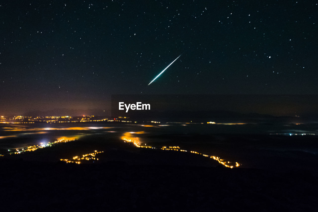 Aerial view of illuminated city against star field at night