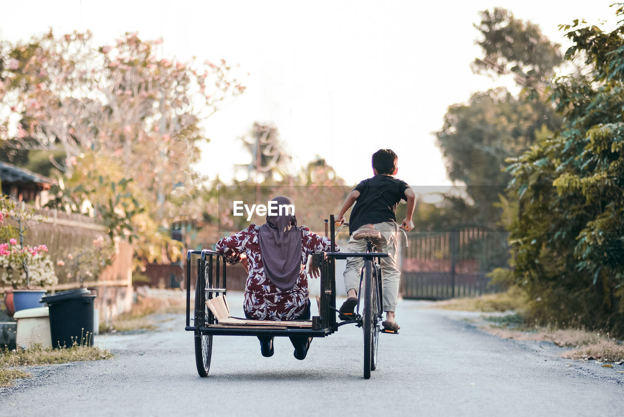 Rear View Of Boy Riding Bicycle With Mother On Road