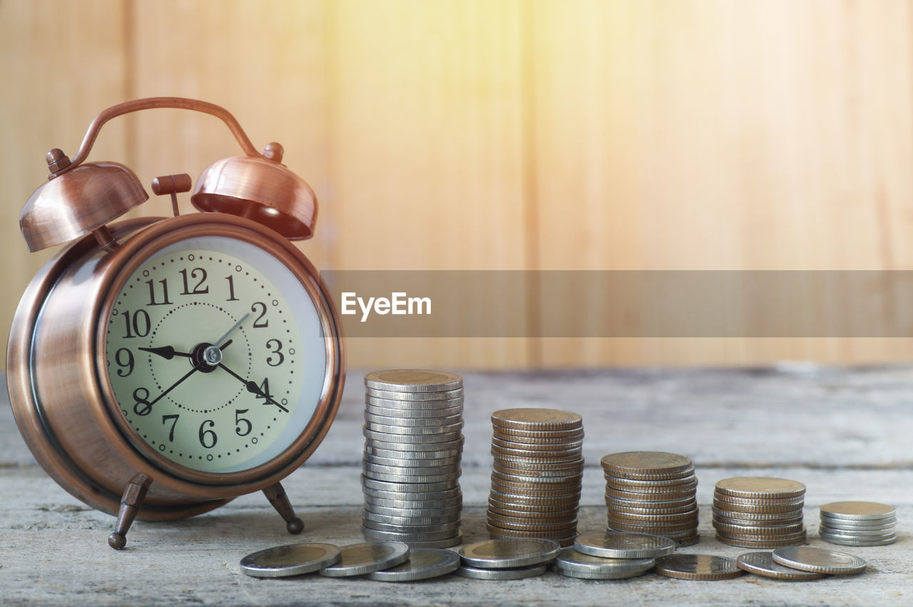 coin, still life, number, alarm clock, no people, finance, clock, stack, large group of objects, table, business, savings, indoors, focus on foreground, time, wealth, close-up, finance and economy, investment, currency, economy
