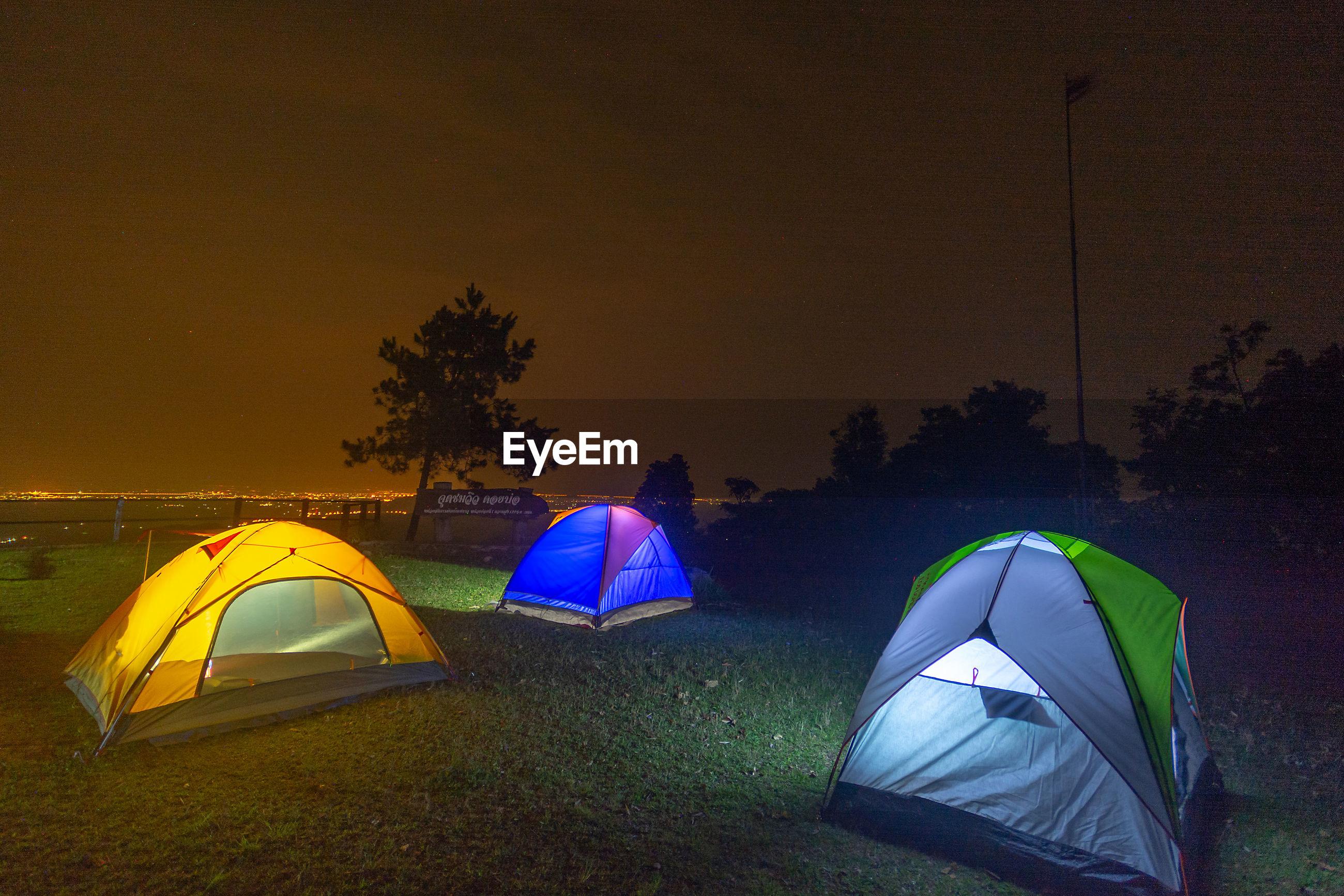 Illuminated tents on land against sky at night