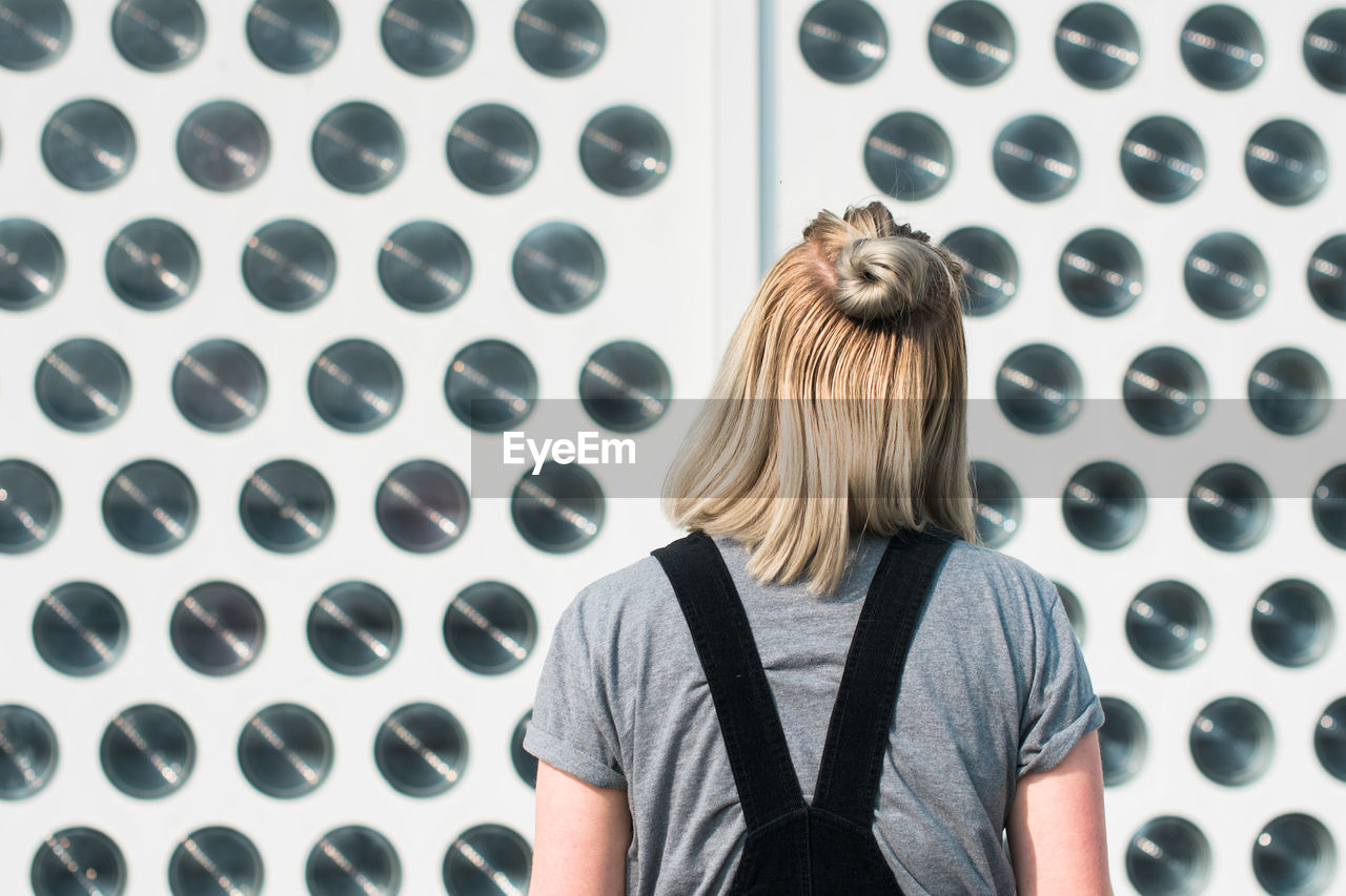 Rear view of woman standing by patterned wall