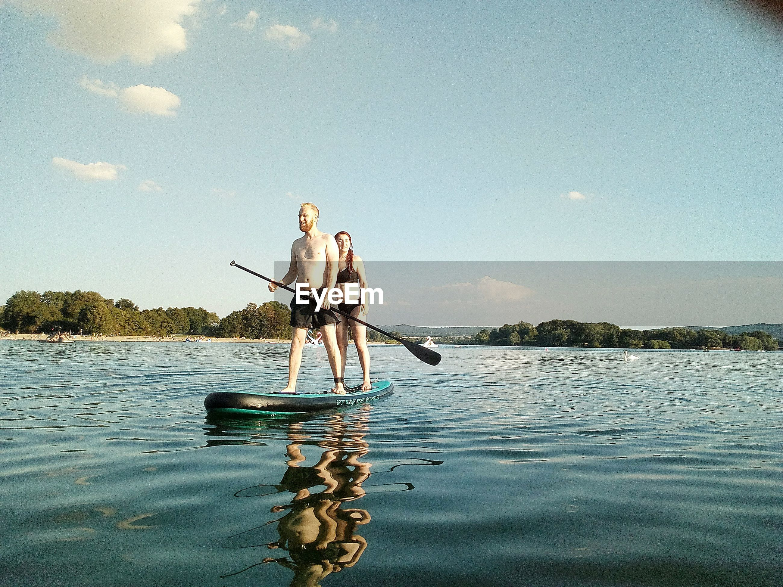 Friends standing on paddleboard in lake against sky
