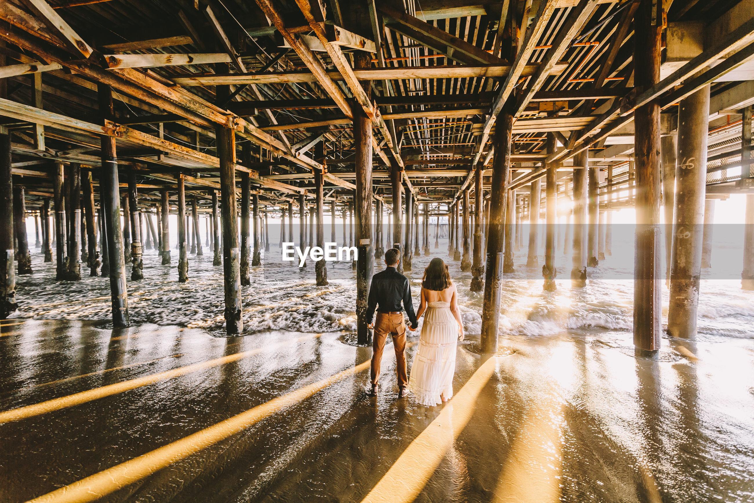 Rear view of couple standing under santa monica pier