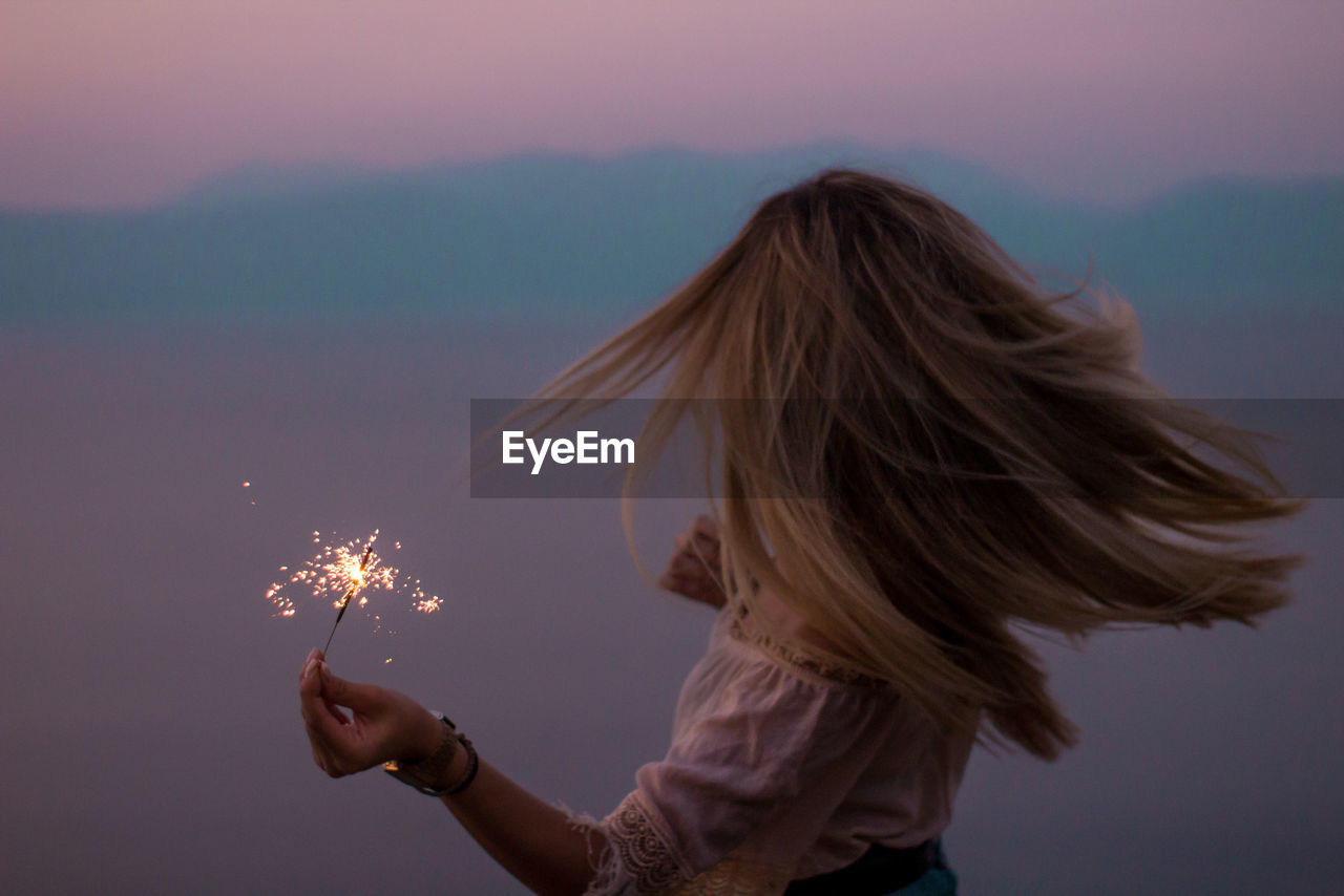 one person, real people, women, leisure activity, lifestyles, sky, firework, nature, holding, illuminated, girls, sparkler, focus on foreground, females, motion, glowing, burning, child, headshot, sparks, hair, firework - man made object, hairstyle, outdoors, firework display, wind