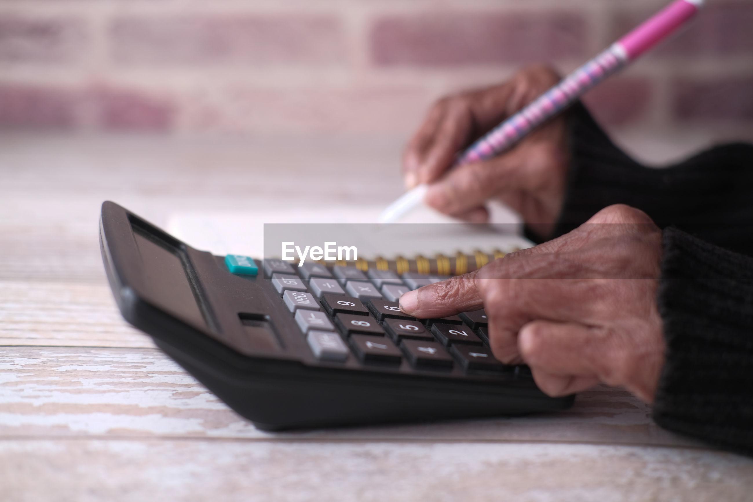 Senior women hand using calculator