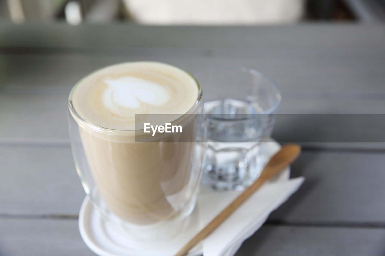 food and drink, coffee, coffee - drink, drink, refreshment, table, still life, coffee cup, frothy drink, mug, spoon, glass, drinking glass, hot drink, cup, eating utensil, focus on foreground, cappuccino, household equipment, indoors, no people, latte, crockery, tray, non-alcoholic beverage, temptation