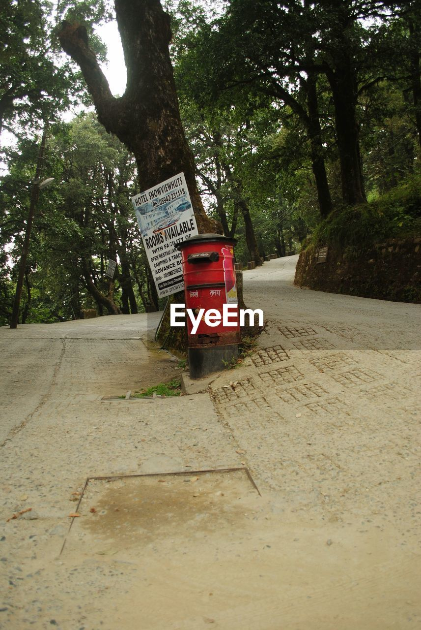 tree, plant, communication, text, container, western script, day, road, nature, sign, outdoors, red, transportation, no people, box, growth, convenience, direction, trunk, tree trunk