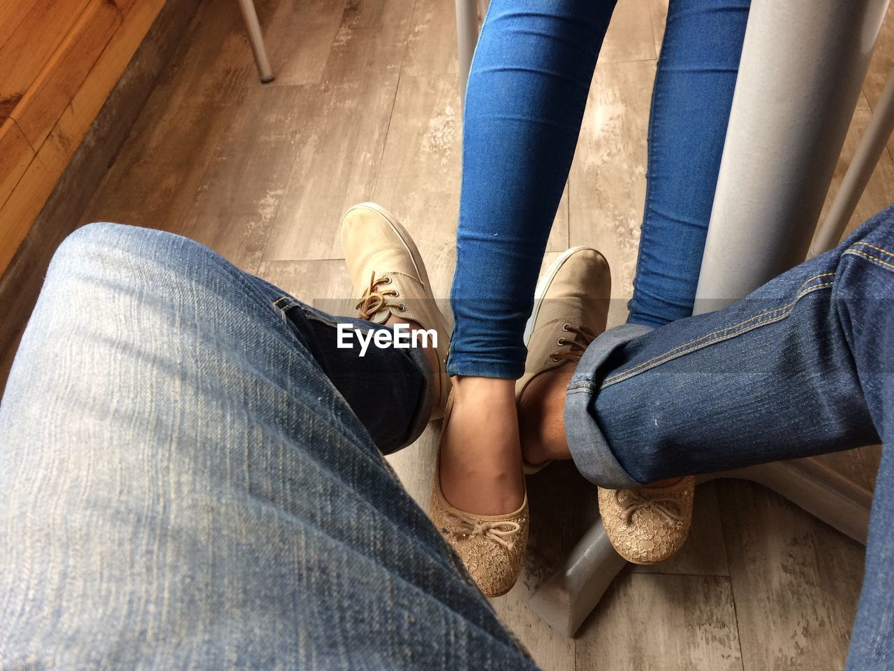 jeans, low section, human leg, shoe, human body part, casual clothing, real people, human foot, lifestyles, leisure activity, day, togetherness, sitting, indoors, men, women, close-up, young women, friendship, young adult, human hand, adult, people, adults only