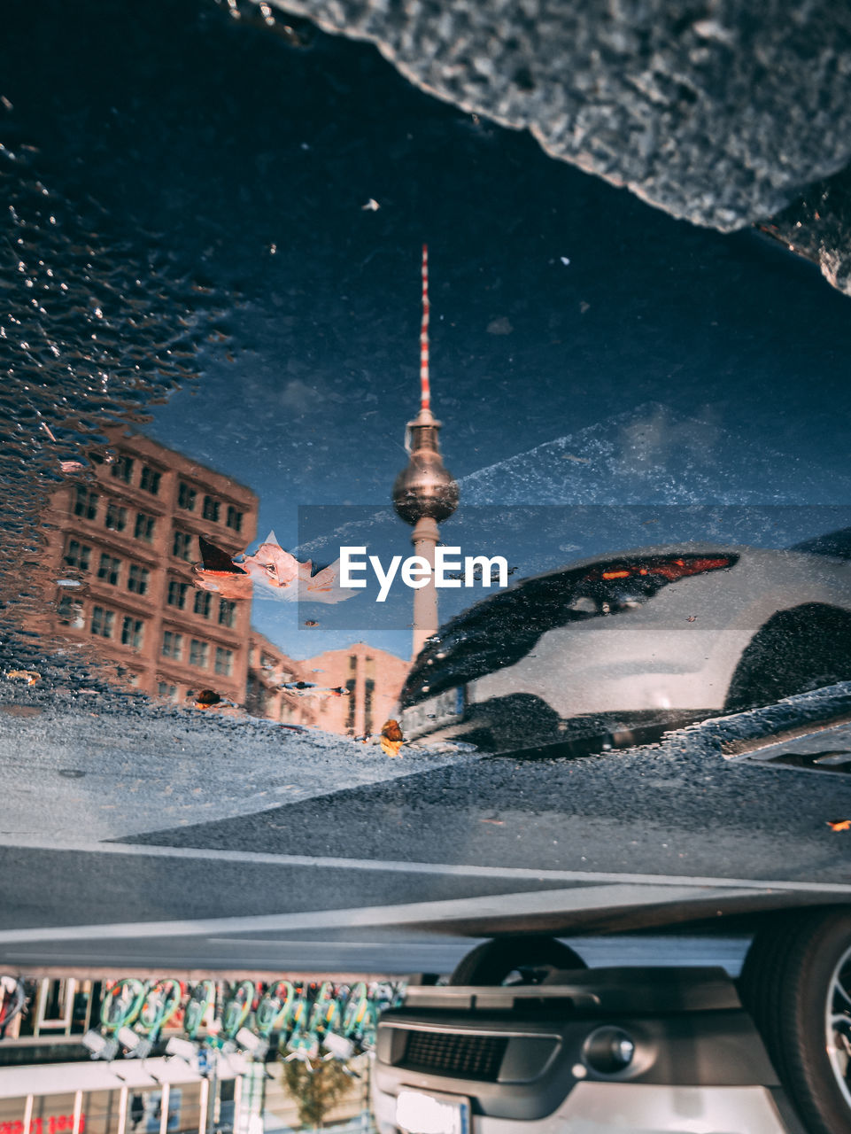 Reflection Of Fernsehturm On Puddle In City