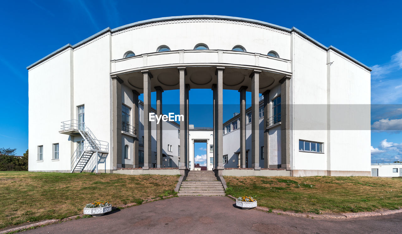 architecture, built structure, building exterior, sky, building, day, nature, no people, footpath, direction, city, clear sky, outdoors, the way forward, entrance, plant, blue, road, transportation, white color