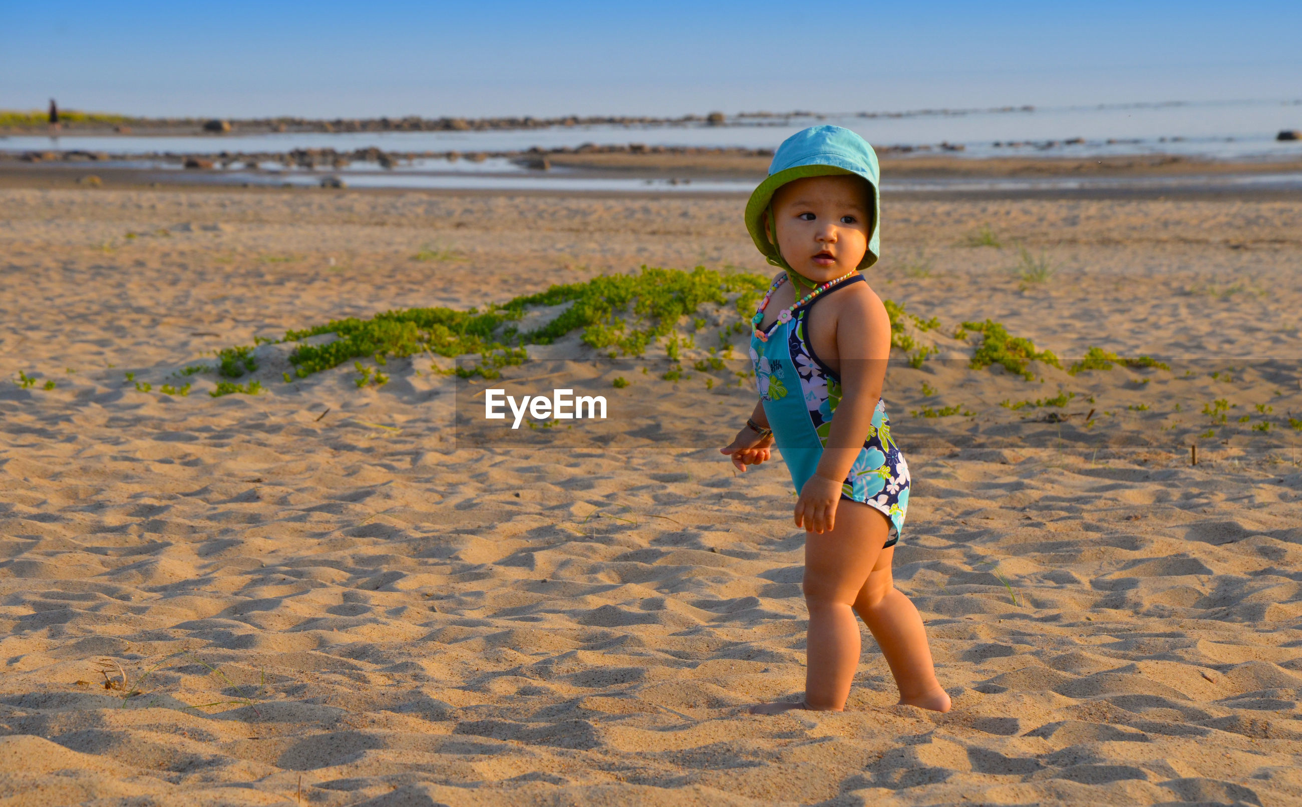 Cute girl looking away while standing on shore of beach