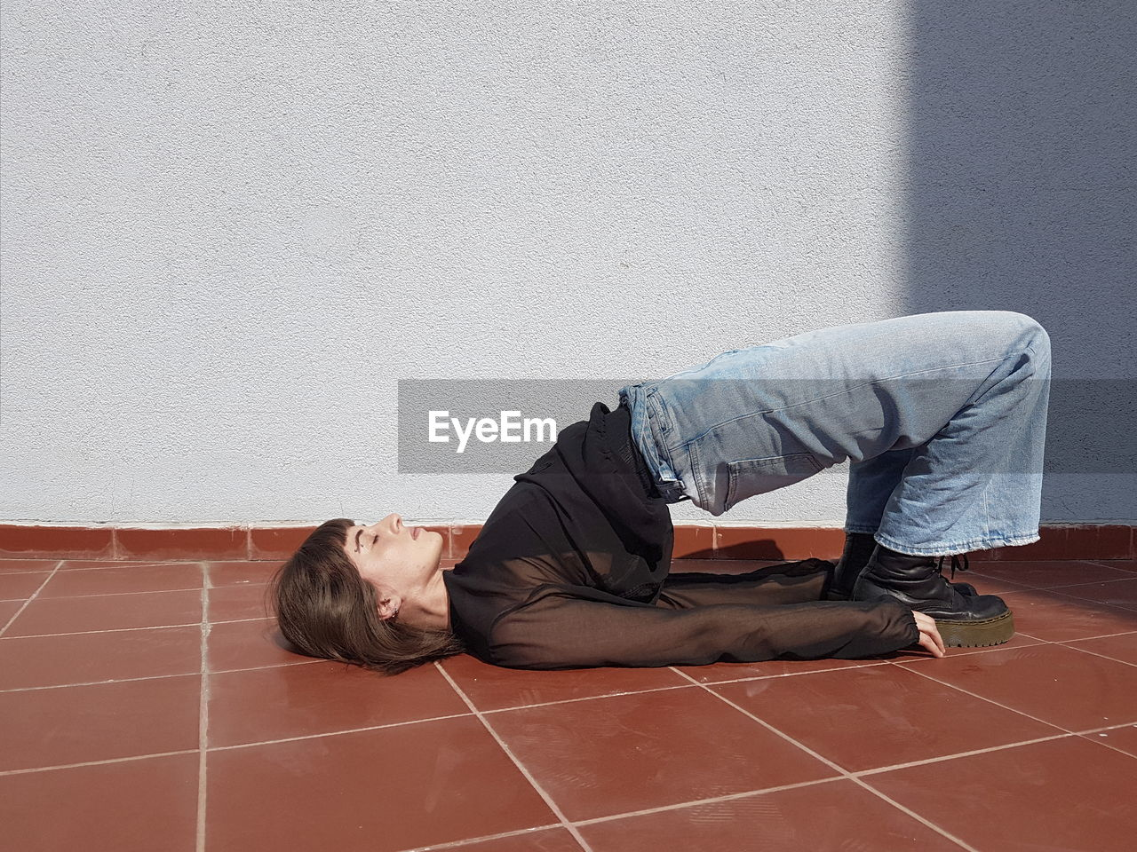 one person, wall - building feature, real people, lifestyles, flooring, men, architecture, young adult, lying down, sadness, day, side view, casual clothing, tile, emotion, copy space, built structure, full length, depression - sadness, tiled floor, social issues