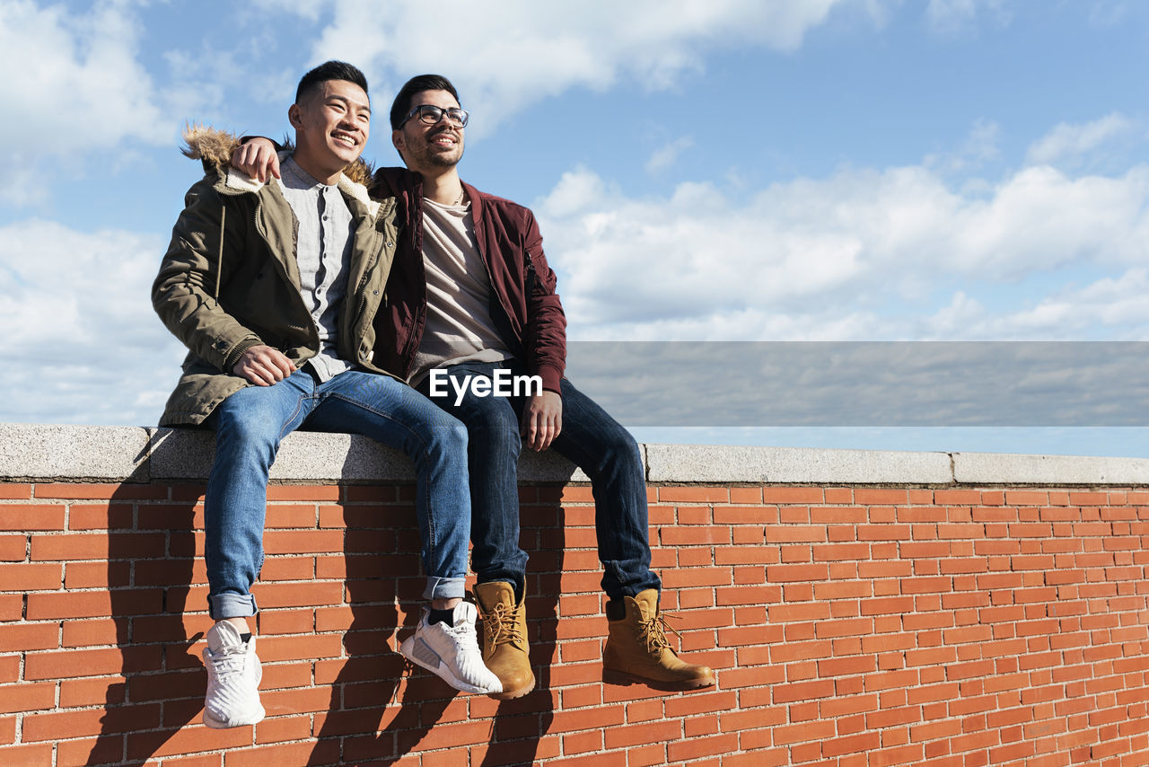 Low angle view of smiling friends sitting on brick wall