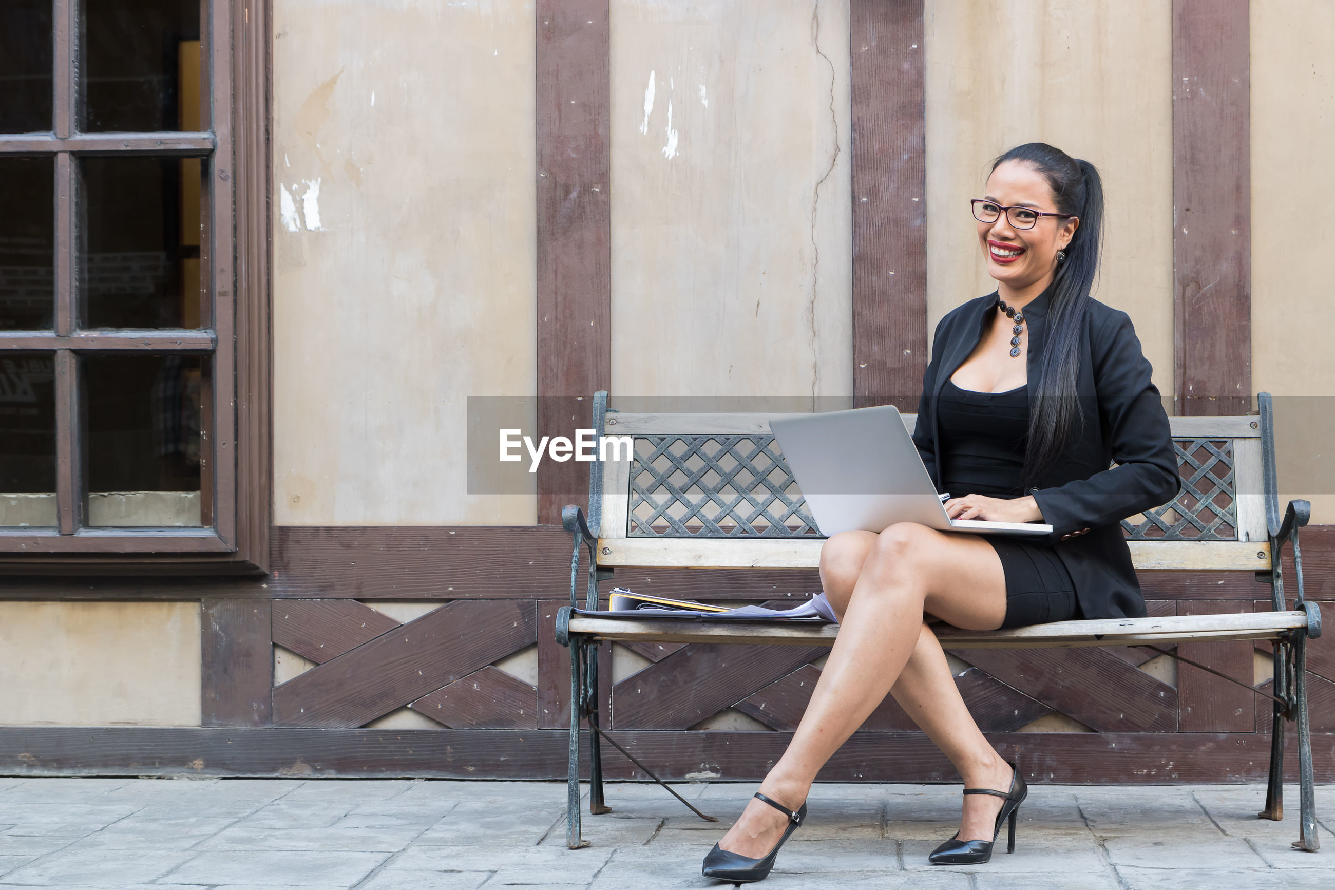 Portrait of businesswoman using laptop on bench