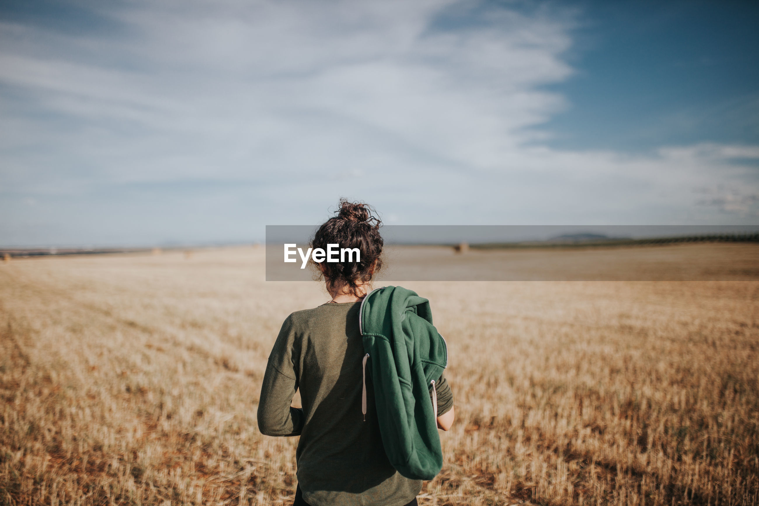 Rear view of woman standing in wheat field against sky