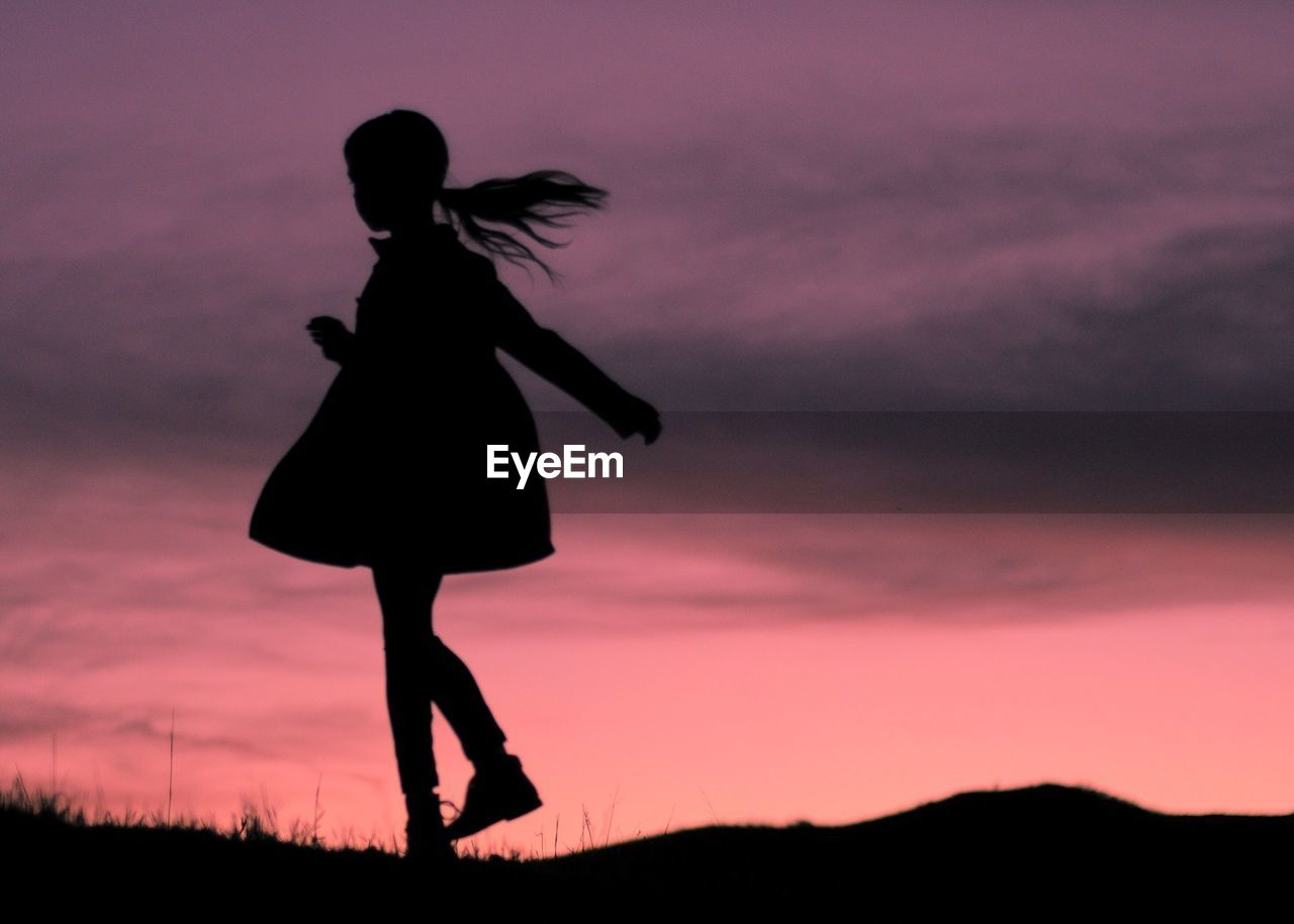 Silhouette Playful Girl On Field Against Sky During Sunset