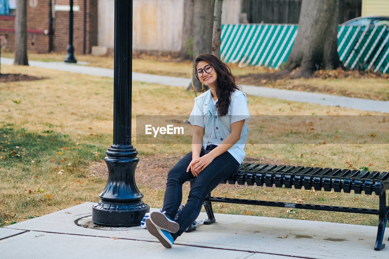 Full Length Portrait Of Smiling Woman Sitting On Bench In Park