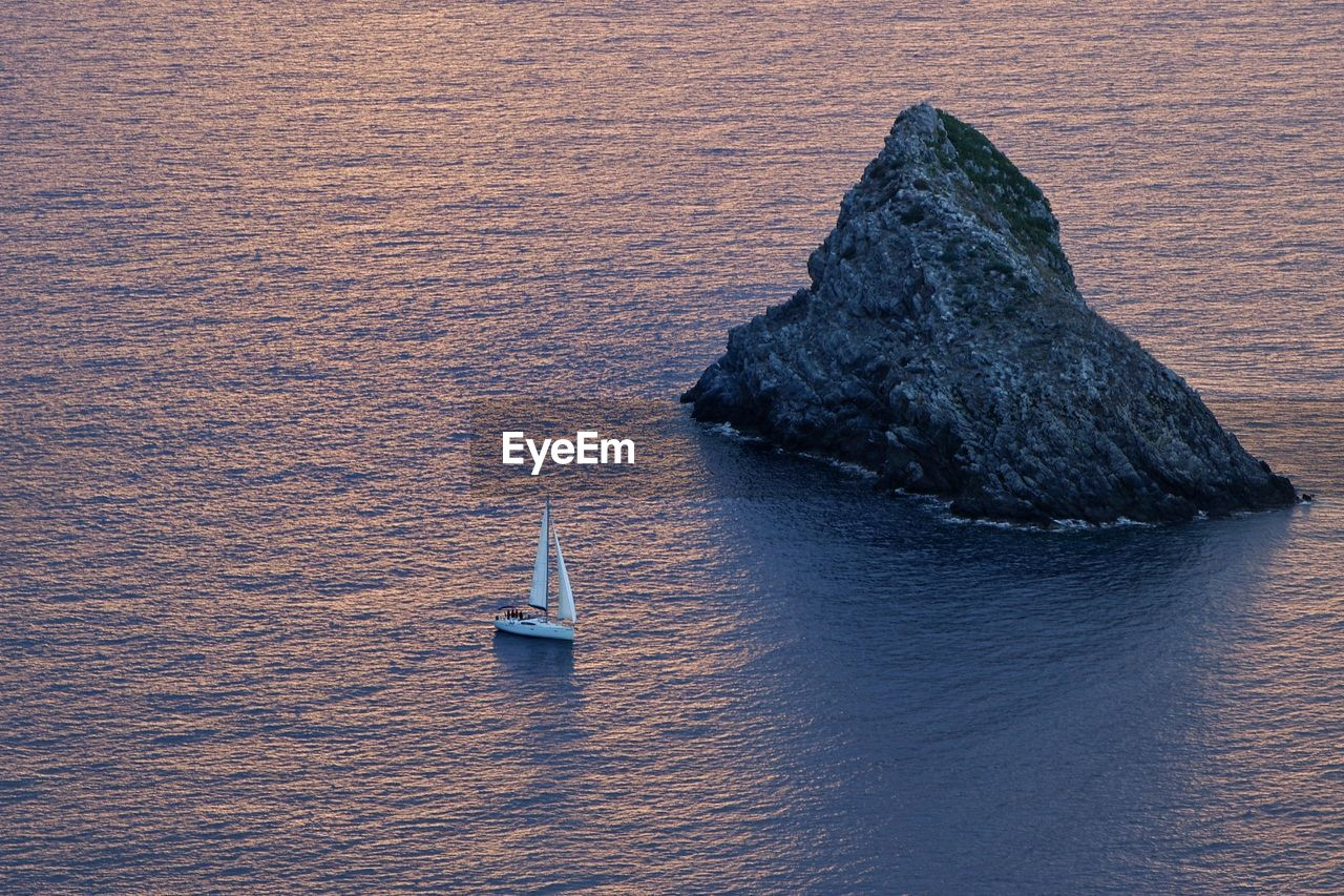 High Angle View Of Rock Formation Amidst Sea During Sunset