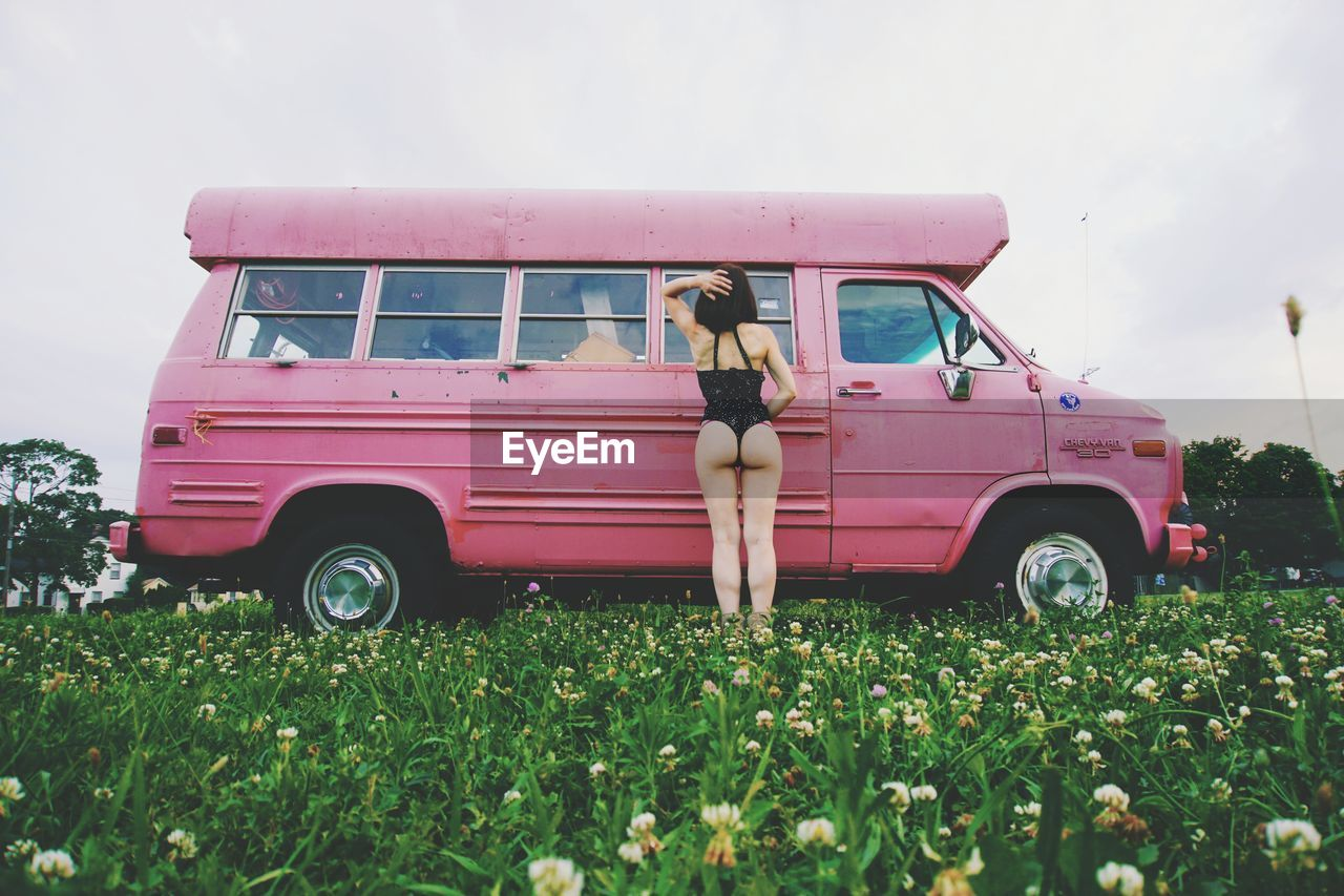Rear View Of Young Woman In Bikini Standing By Car On Grassy Field Against Clear Sky