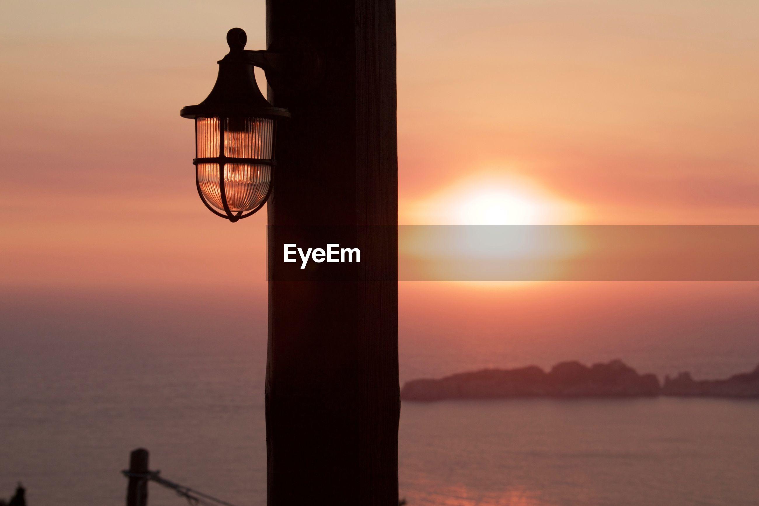 SILHOUETTE LAMP BY SEA AGAINST ORANGE SKY
