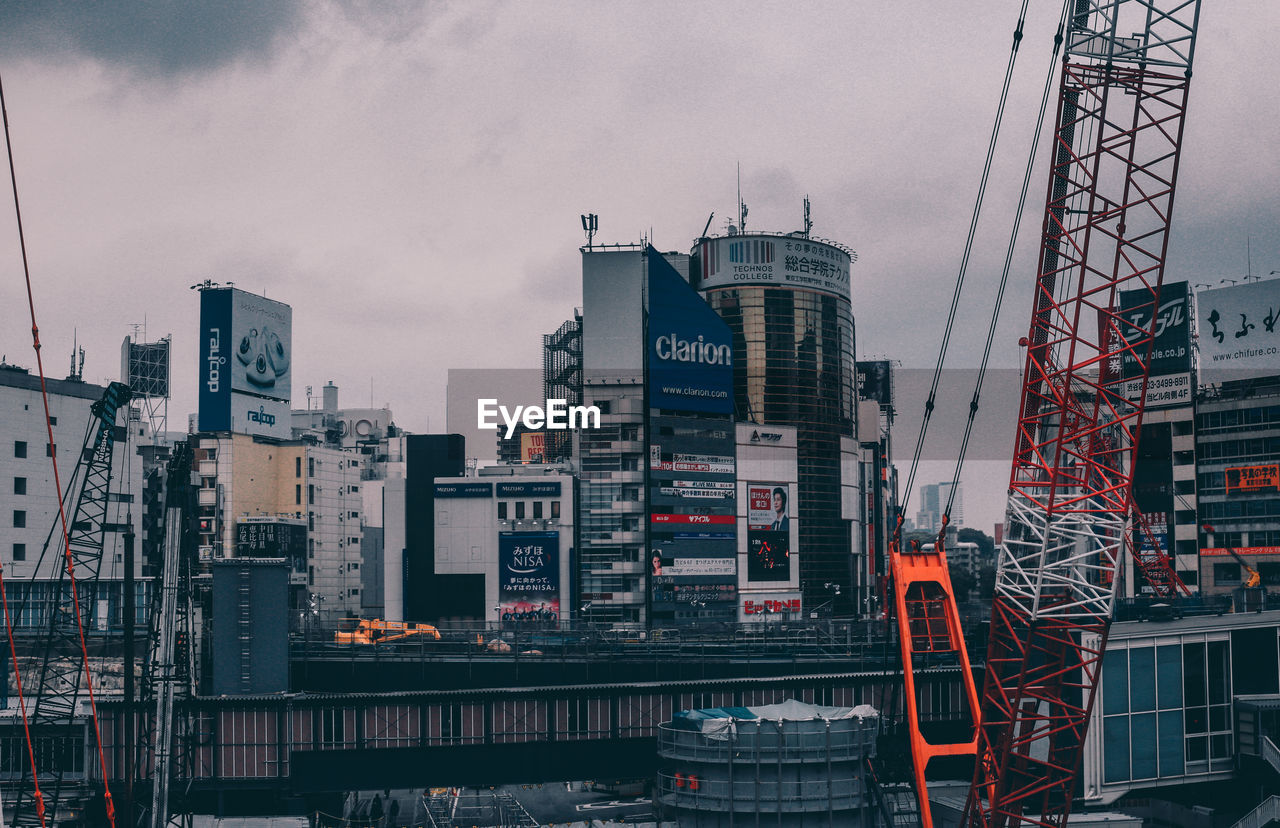 View Of Crane In City Against Sky