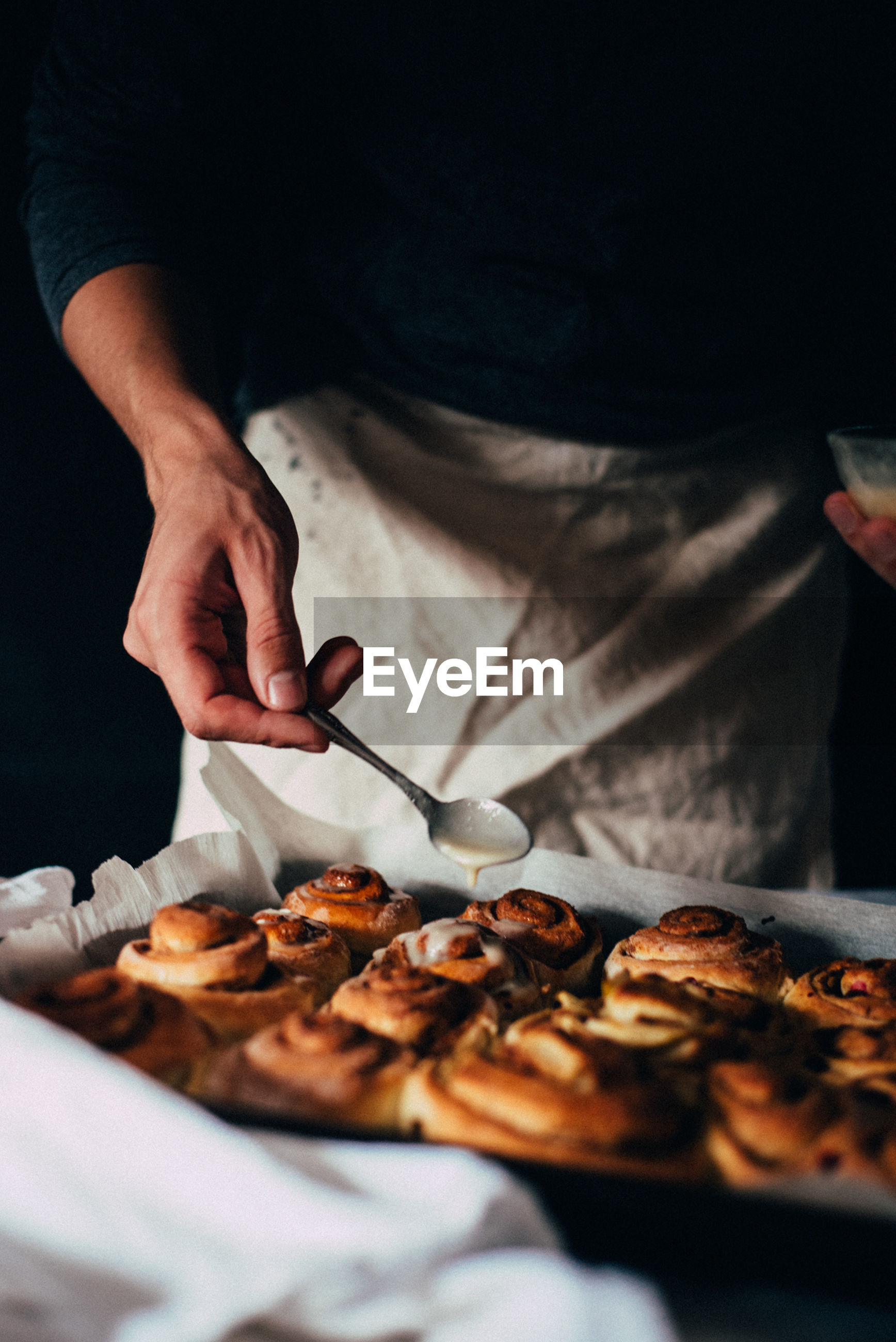 Midsection of person making cinnamon buns in tray