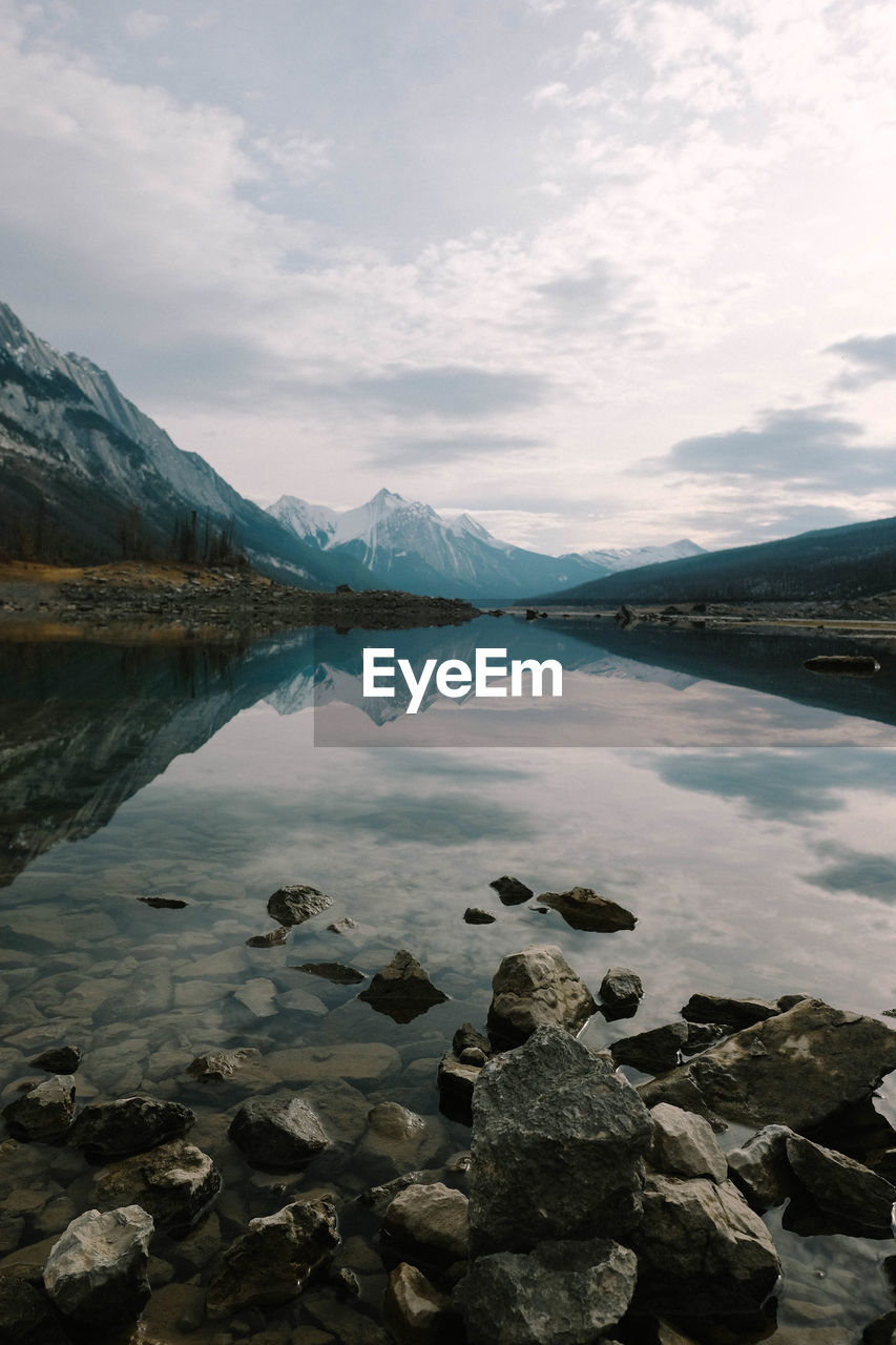 water, sky, cloud - sky, mountain, beauty in nature, lake, scenics - nature, tranquil scene, tranquility, rock, reflection, rock - object, solid, nature, mountain range, day, no people, non-urban scene, outdoors, snowcapped mountain, mountain peak