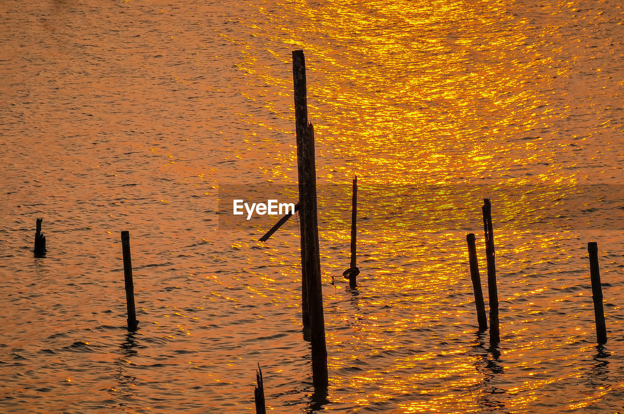 wood - material, water, post, waterfront, nature, no people, wooden post, orange color, yellow, outdoors, sunset, day, metal, beauty in nature, reflection, high angle view, lake, tranquility