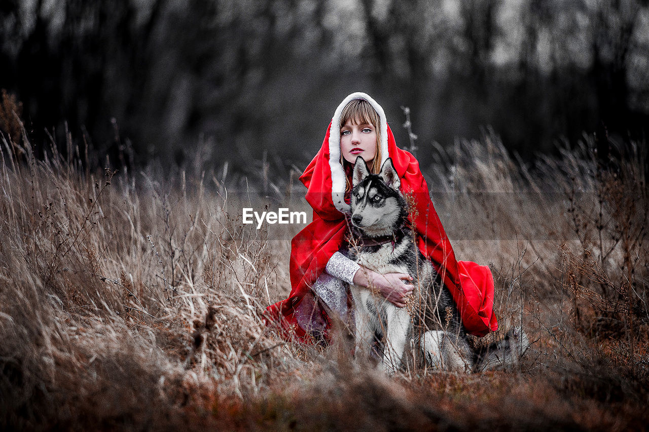 Portrait Of Woman With Dog On Field In Forest