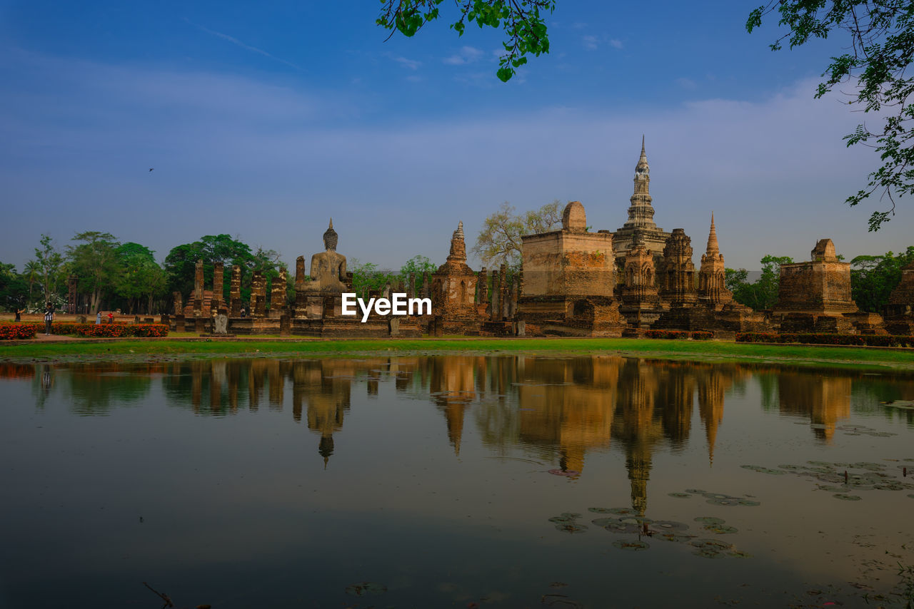 Pond by wat mahathat temple against sky