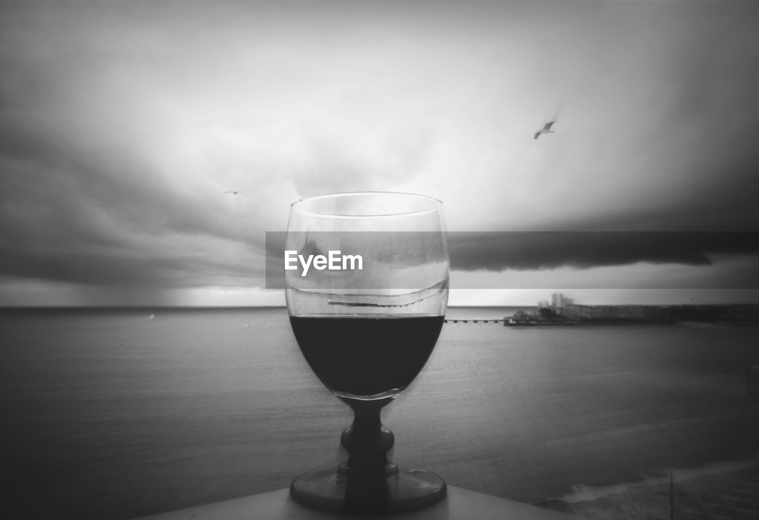 food and drink, drink, refreshment, drinking glass, sea, water, horizon over water, sky, freshness, alcohol, glass - material, close-up, table, focus on foreground, cloud - sky, sunset, transparent, indoors, no people, drinking straw