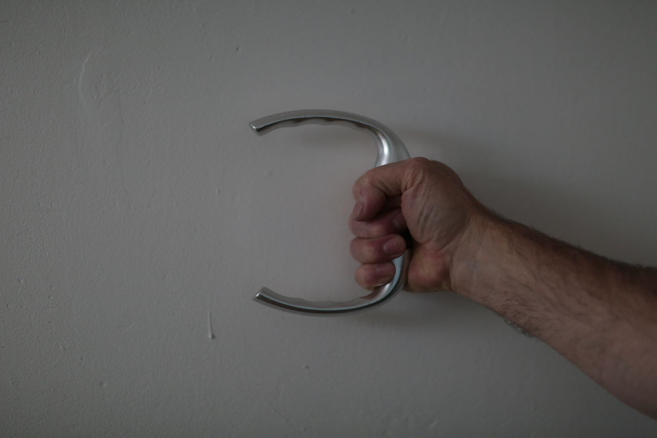 Cropped hand of man holding handle by white wall