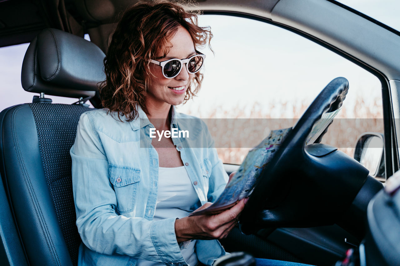 Smiling woman wearing sunglasses reading map in car