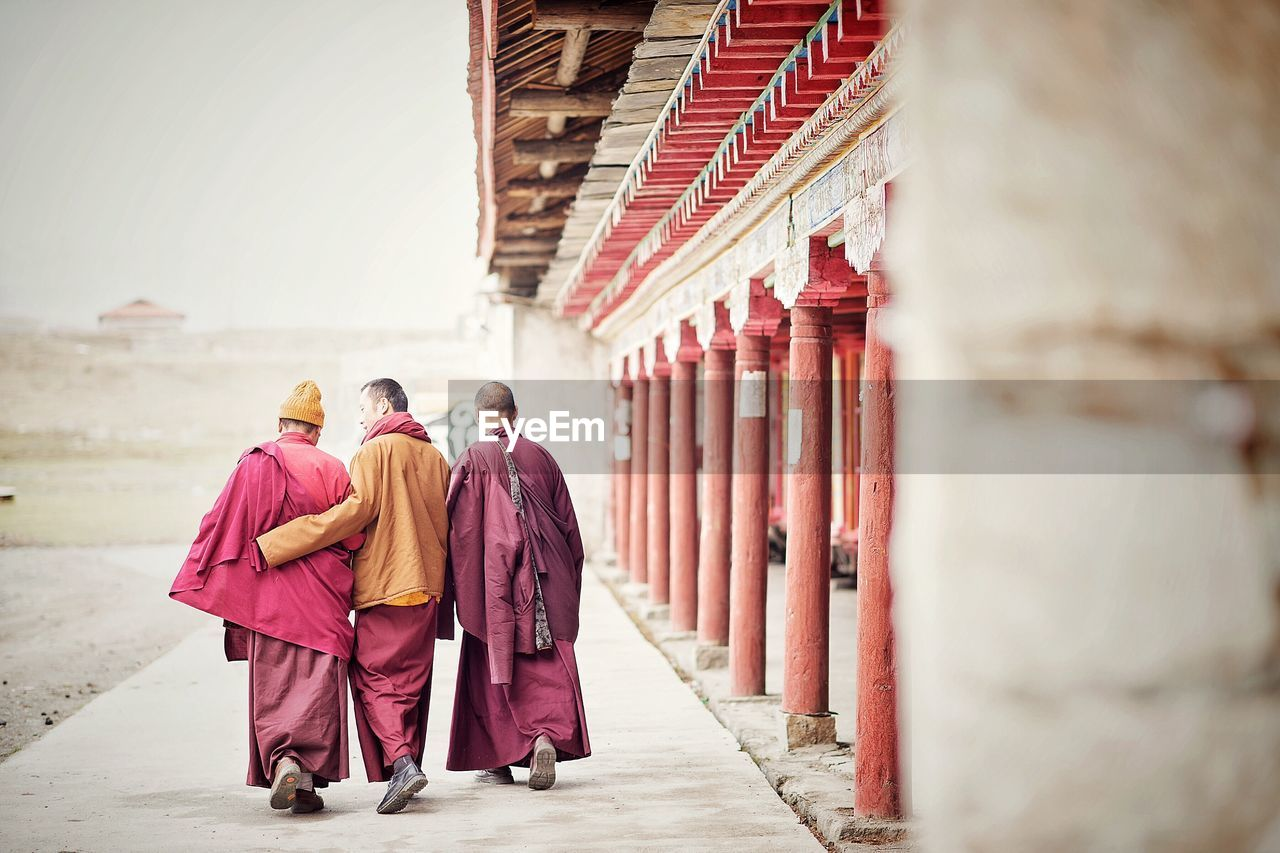 Rear View Of Monks Walking On Walkway By Temple