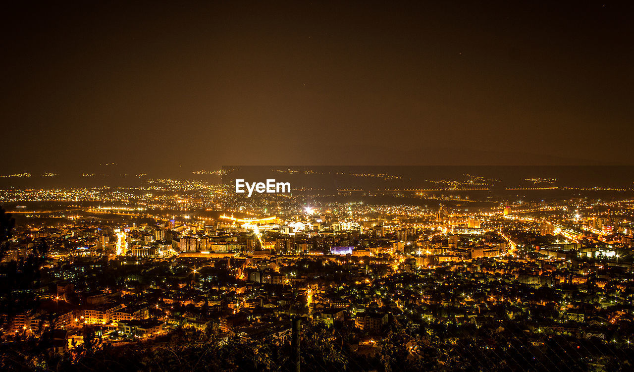 building exterior, cityscape, city, architecture, illuminated, built structure, night, building, crowd, high angle view, sky, aerial view, crowded, nature, residential district, outdoors, copy space, city life, glowing, office building exterior, skyscraper