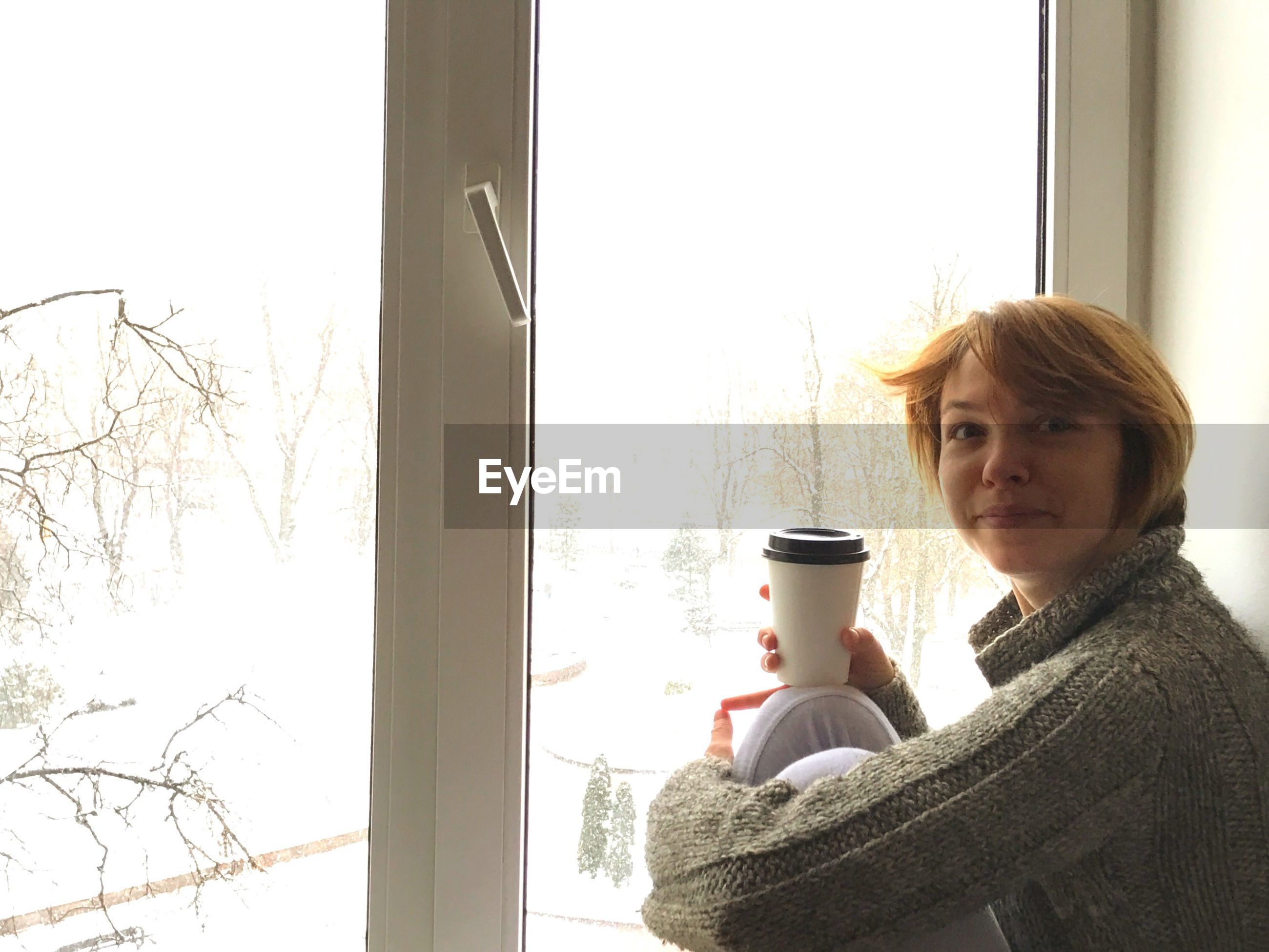 Portrait of woman holding coffee cup by window at home