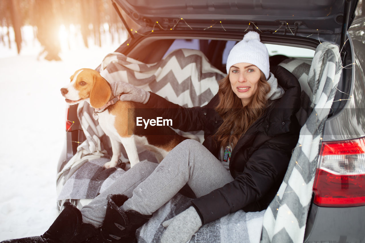 Portrait of smiling young woman with dog sitting in car trunk