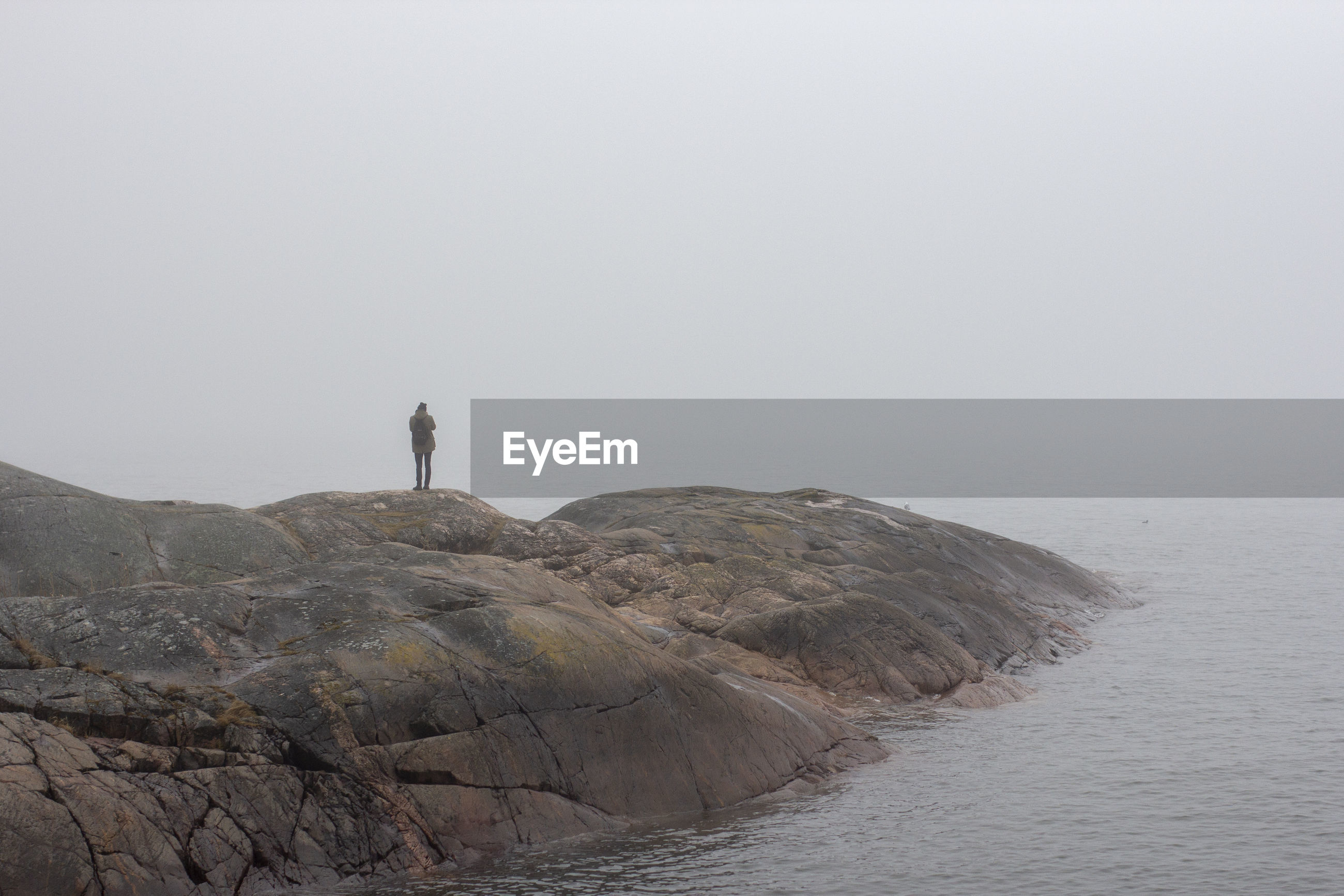 MAN STANDING ON ROCK BY SEA AGAINST SKY DURING FOGGY WEATHER