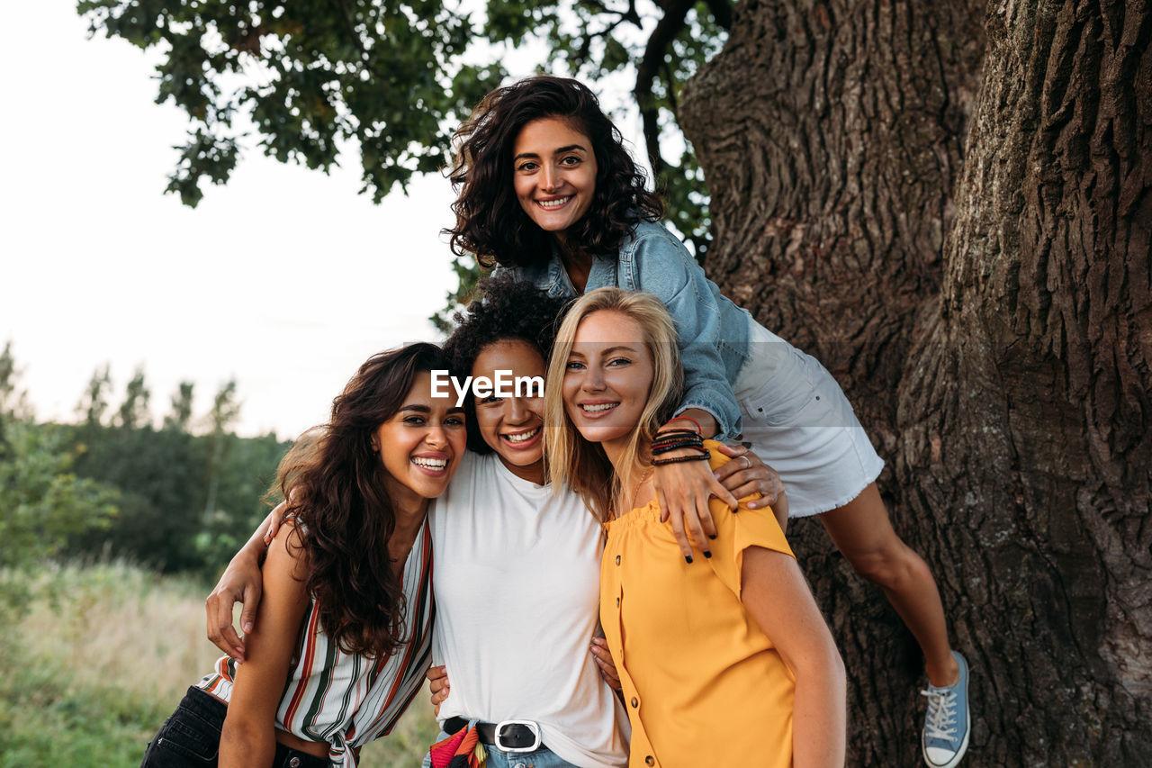 Portrait of smiling female friends near tree trunk