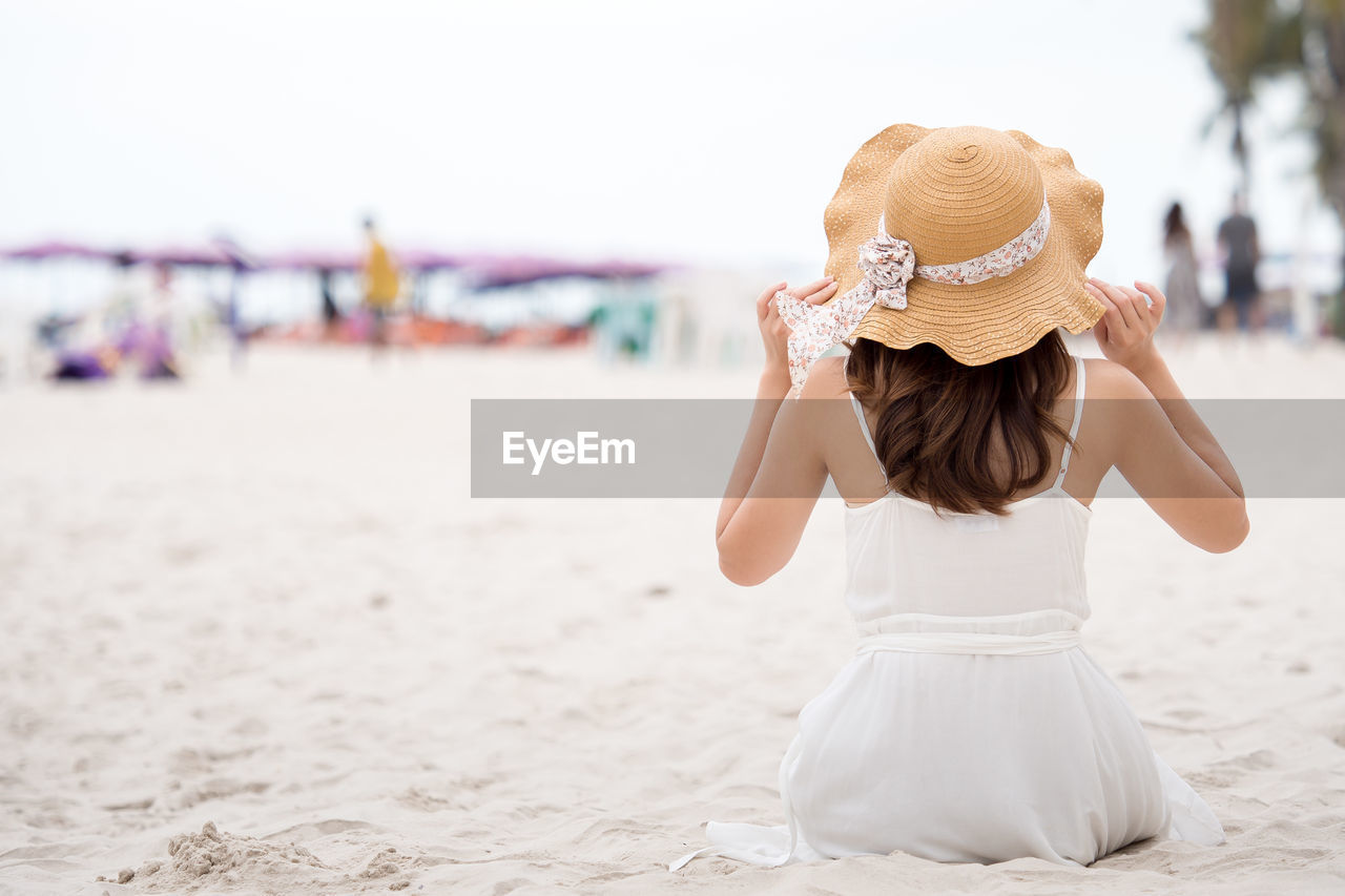 Woman wearing hat while sitting at beach