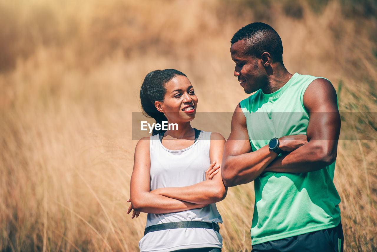 Couple with arms crossed looking at each other