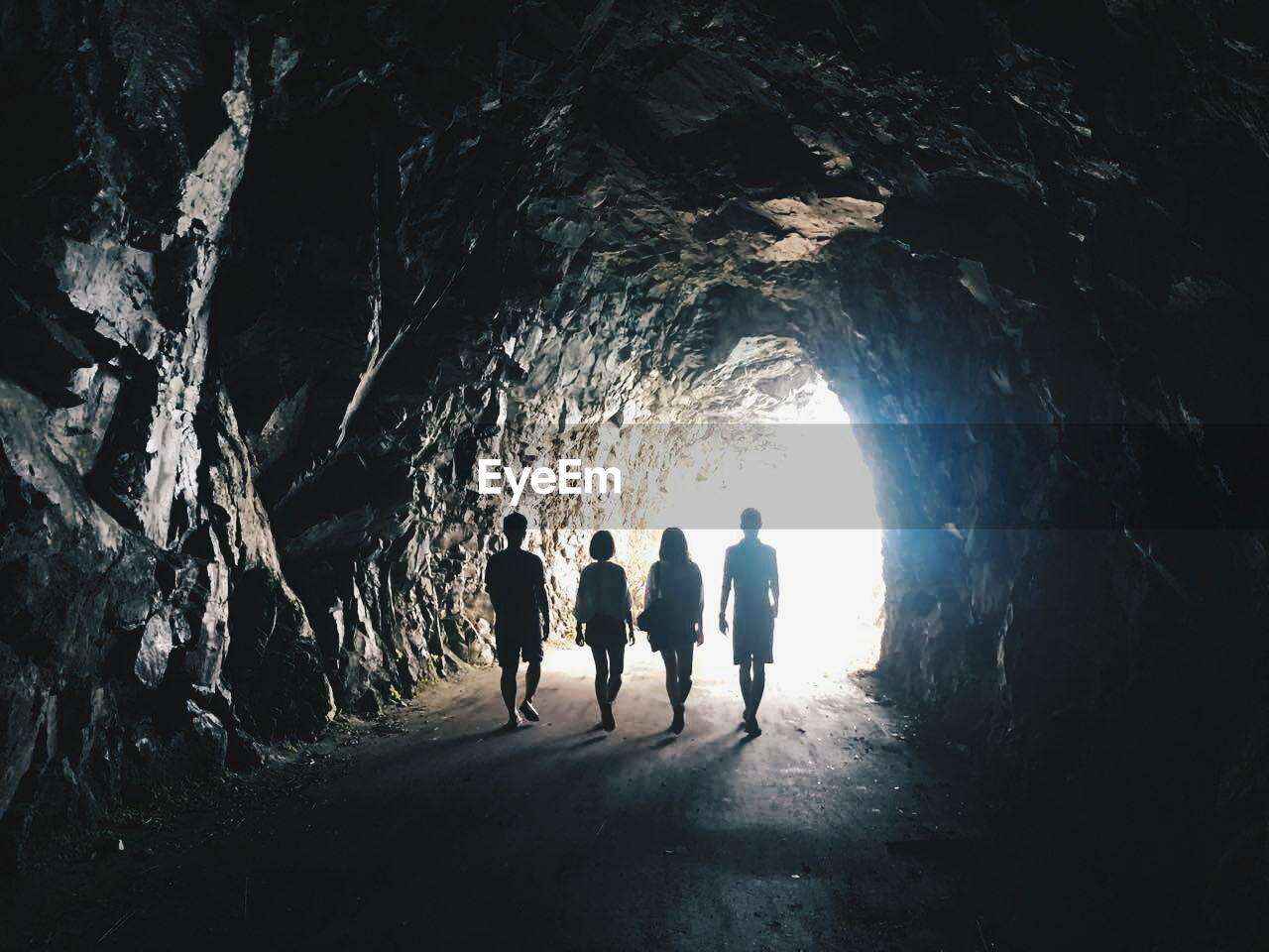 Rear View Full Length Of Friends Walking In Tunnel