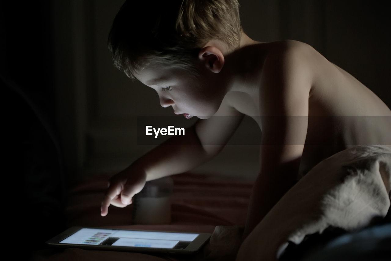 Close-up of shirtless boy using digital tablet at home