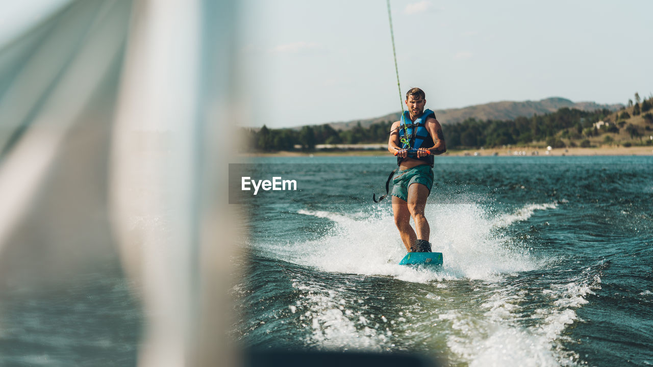 Full length of man wakeboarding in sea