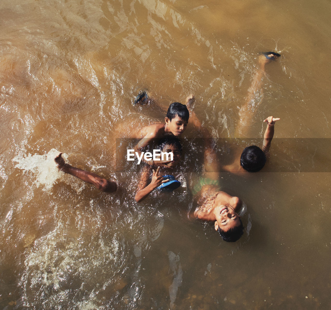 water, high angle view, group of people, leisure activity, nature, swimming, men, lifestyles, waterfront, people, togetherness, real people, enjoyment, shirtless, day, outdoors, motion