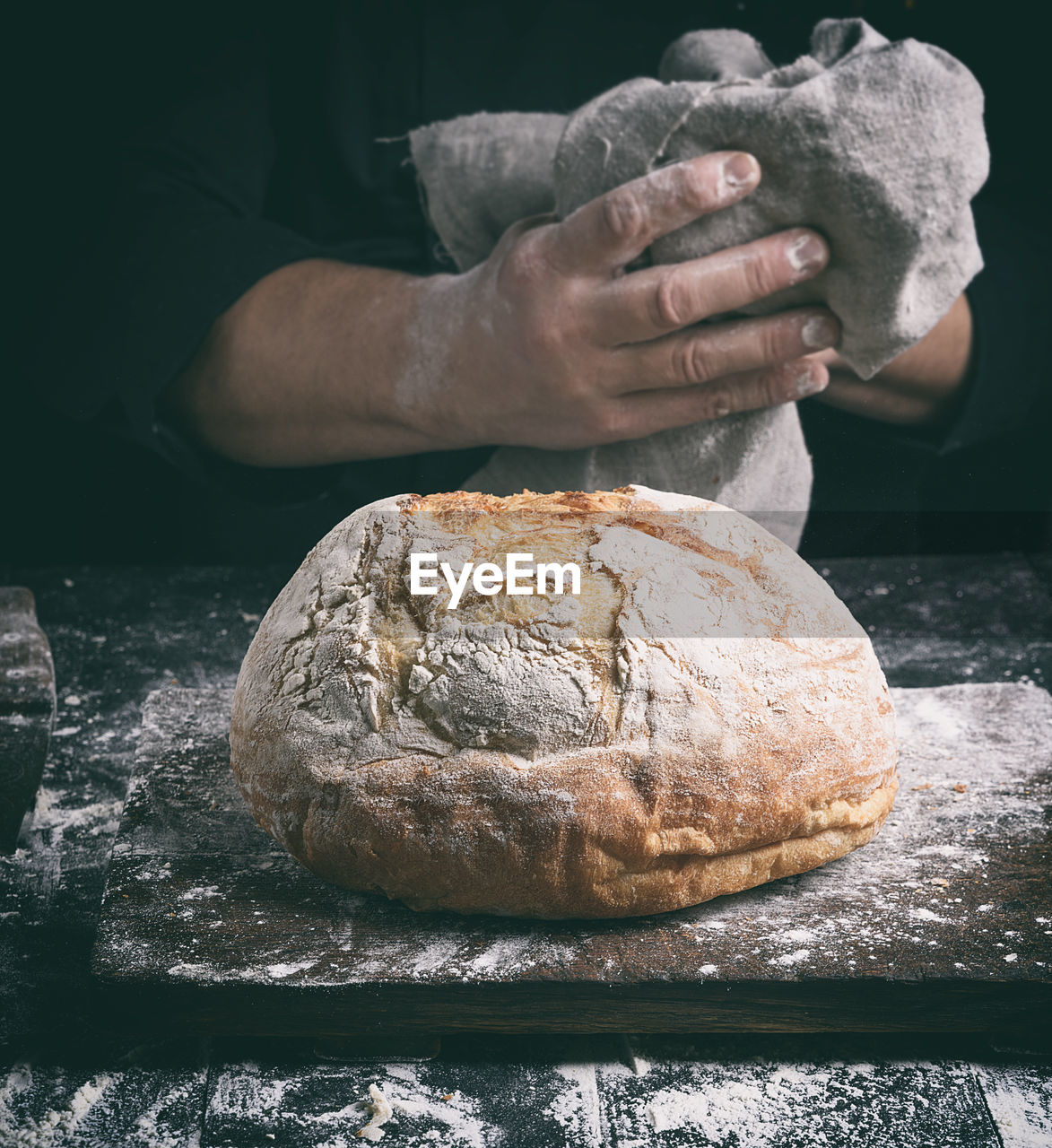 Close-Up Of Person With Bread At Counter