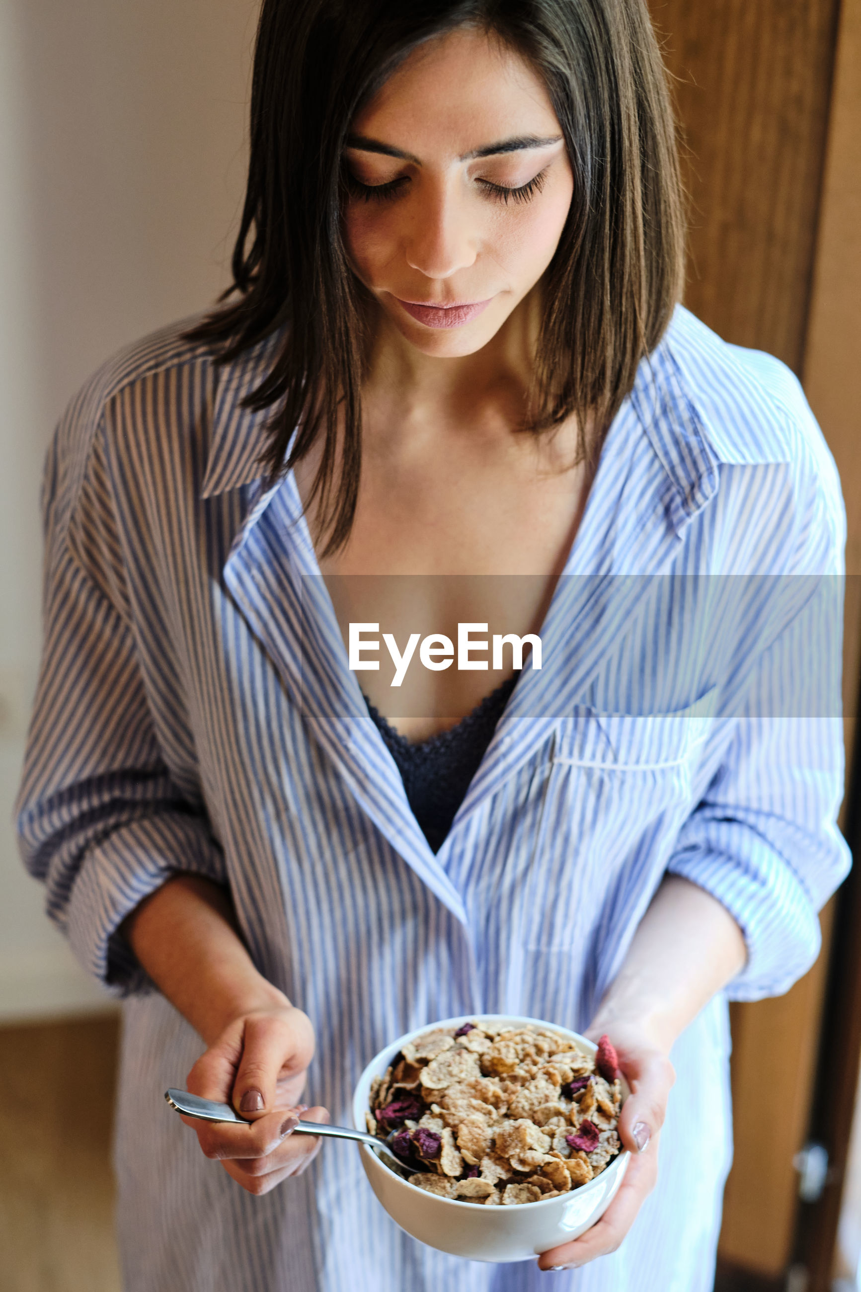 MIDSECTION OF A WOMAN HOLDING ICE CREAM IN PLATE