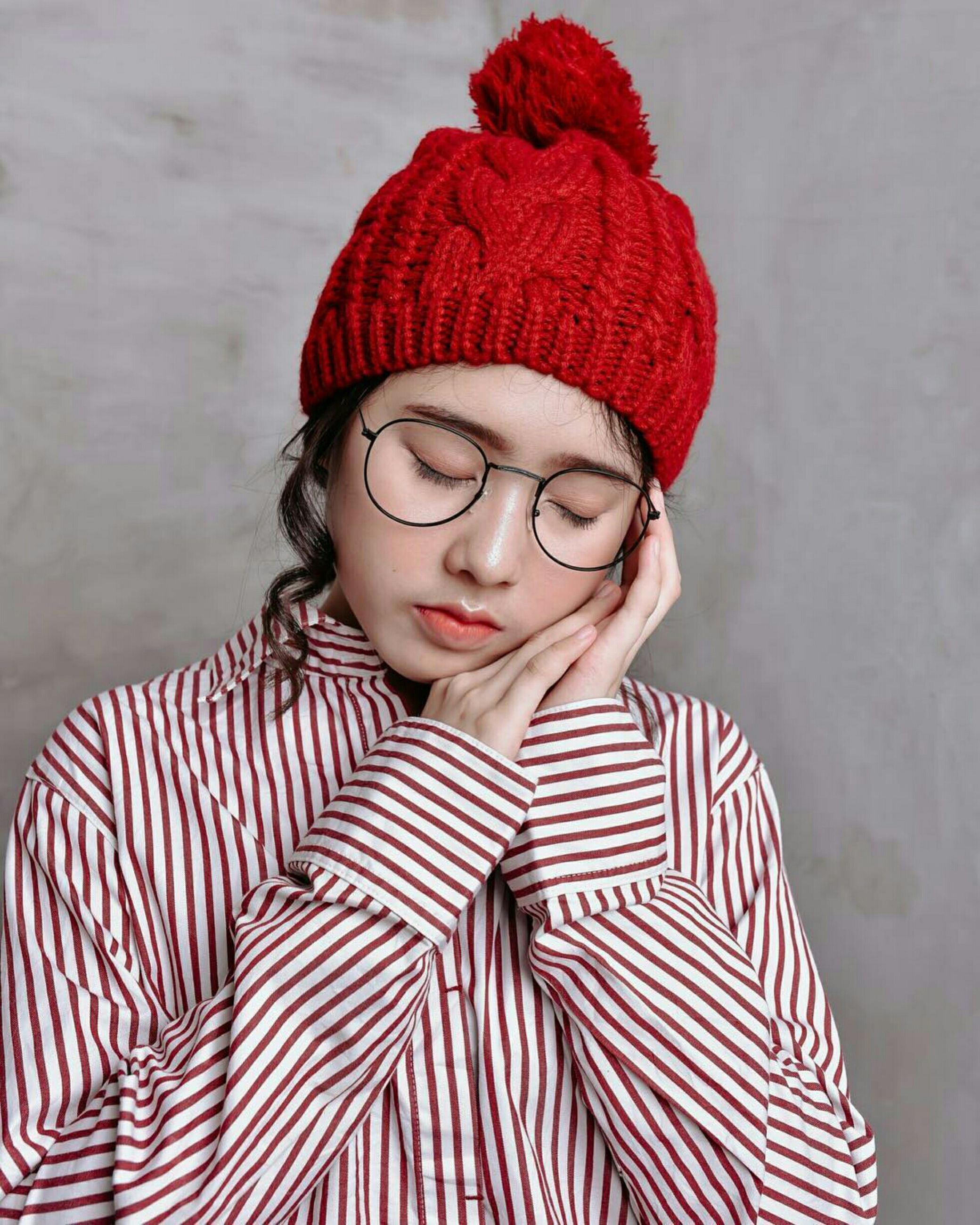 Close-up of young woman with eyes closed against wall