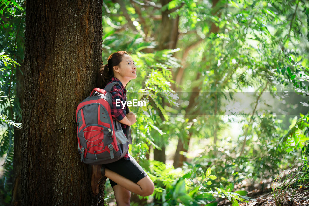 Thoughtful female hiker carrying backpack while leaning on tree trunk in forest