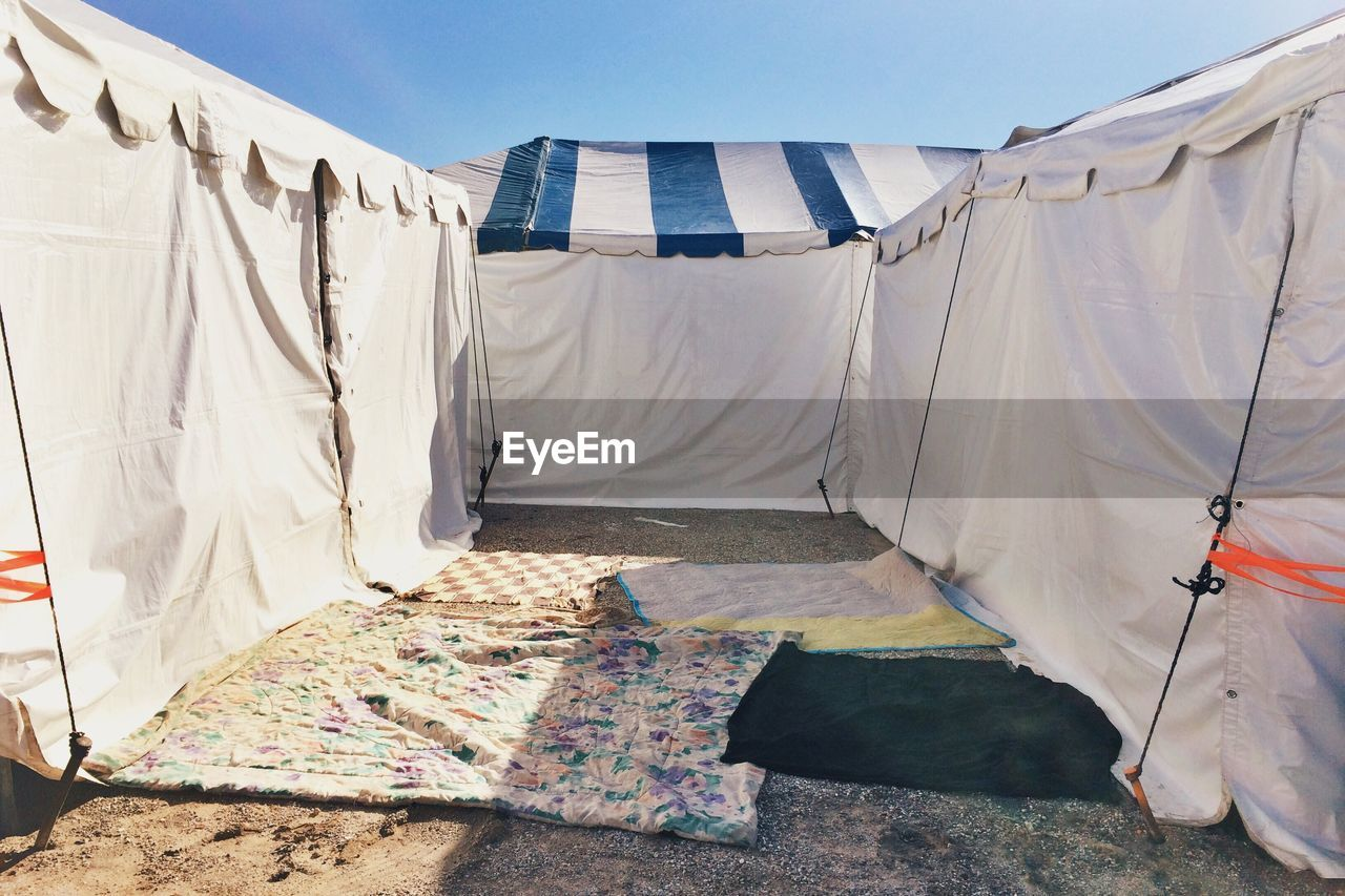 Tents and fabric against blue sky